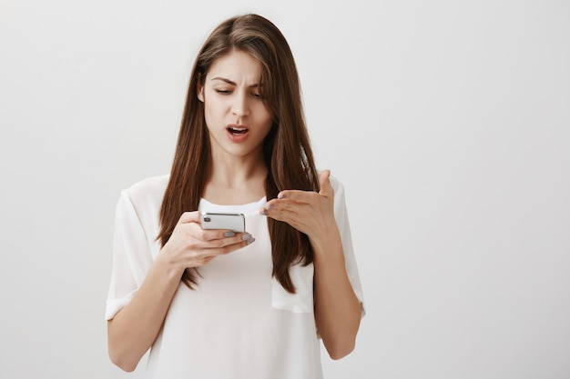 Frustrated woman complaining at something, pointing bothered at mobile phone display