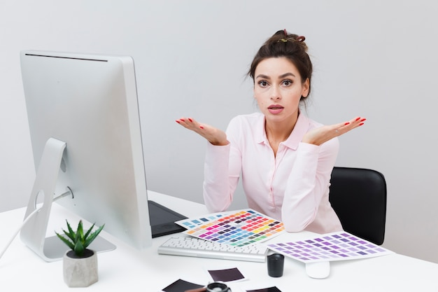 Frustrated woman at desk surrounded by color palettes