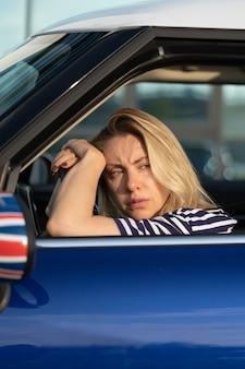 차 안의 좌절된 여성 운전자는 견인차를 기다립니다. 슬픈 여성은 차를 부수는 데 지쳤습니다. 좌석에 앉아