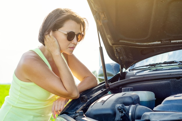 Frustrated woman driver near broken car.