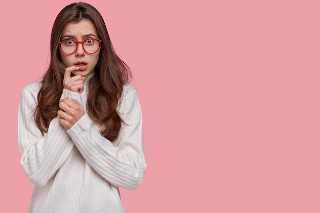 欲求不満の女性は緊張した表情で手を口の近くに保ち、戸惑いながら見える