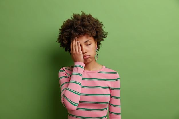 좌절 한 여자는 야간 근무를 한 후 피곤한 표정으로 에너지 부족으로 얼굴을 손바닥으로 기울이고 머리가 녹색 벽에 캐주얼 점퍼 포즈를 입습니다.