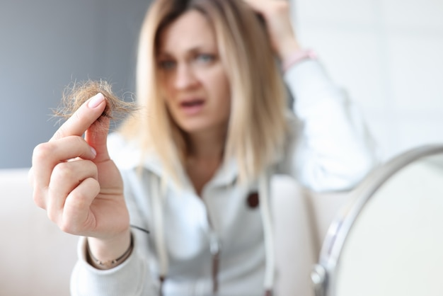 Frustrated woman holds bun of her hair in her hand. hair loss concept