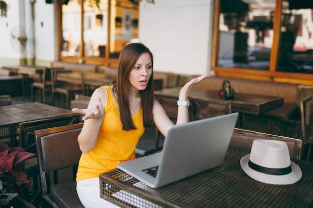 現代のラップトップpcコンピューター、自由時間のレストランで作業しているテーブルに座っている屋外通りのコーヒーショップカフェで欲求不満の女性