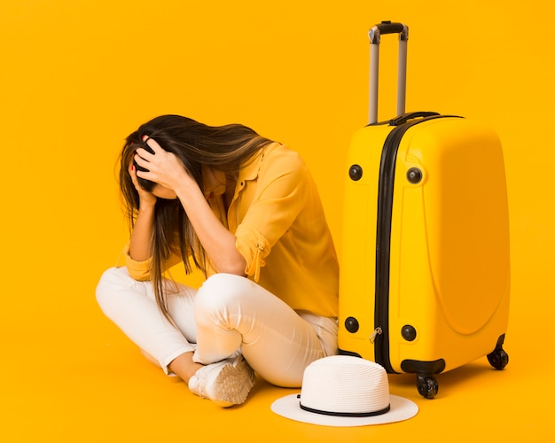 Frustrated woman next to luggage and hat