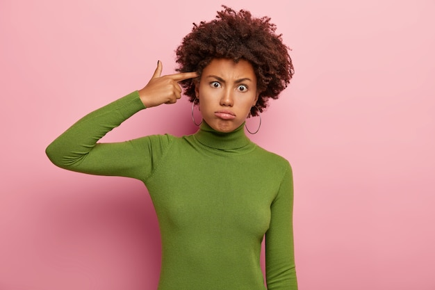 Frustrated woman makes suicide gesture, keeps index finger on temple, tilts head, sighs from tiredness, wears casual green turtleneck, looks with unhappy expression