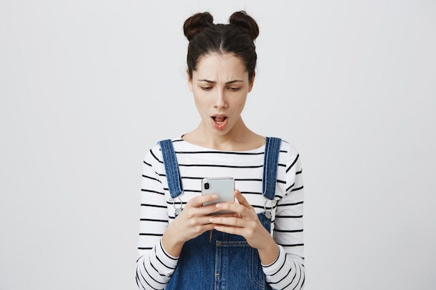 Разочарованная женщина, читающая сообщение на смартфоне