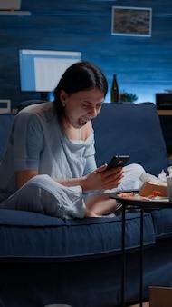 Разочарованная женщина кричит и выбрасывает телефон после прочтения уведомления о прекращении банковского обслуживания
