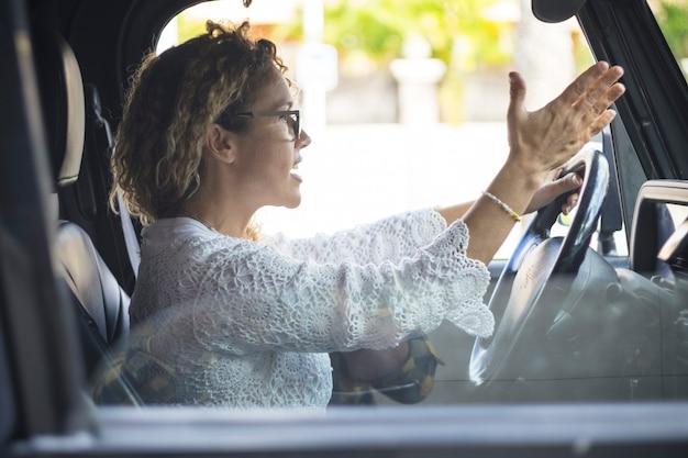 車を運転中に叫んで欲求不満の女性。交通渋滞で車を運転している女性を強調しました。昼間の道路交通中に誰かと議論しながら手で身振りで示す彼女の車を運転する失礼な女性