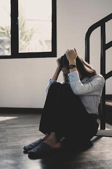 孤独、動揺、悲しみ、不幸、落ち込んでいると感じて苦しんでいる家に一人で座っている欲求不満の女性。