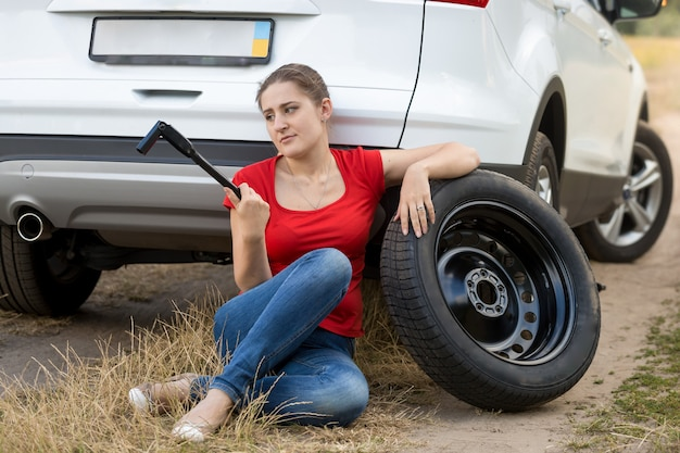 Frustrated woman sitting next to broken car and trying to change flat tire