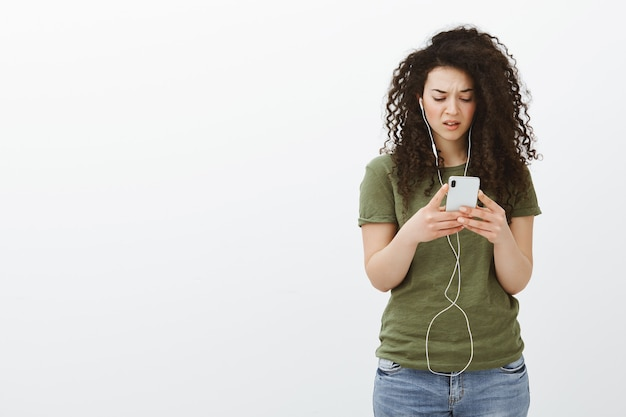 Frustrated woman staring at smartphone cluelessly. portrait of confused displeased curly-haired woman in casual outfit