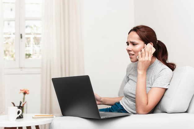 Frustrated woman talking on the phone while looking at laptop