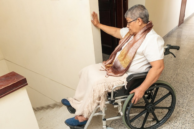 Frustrated woman in a wheelchair because she can't go down the stairs