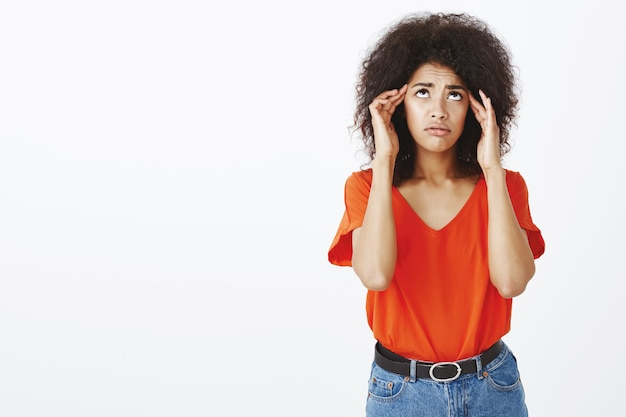 Frustrated woman with afro hairstyle posing in the studio