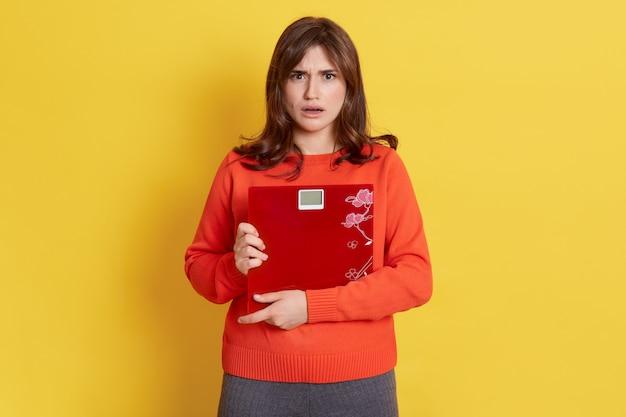 노란색에 고립 된 규모 포즈와 좌절 된 여자, 매우 화가 슬픈 여자, 그녀의 체중을 제어하는 여성