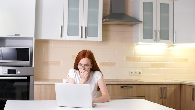Разочарованный женщина, работающая из дома на своем компьютере