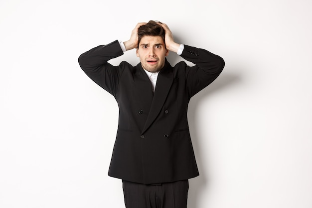 Frustrated and worried businessman in black suit, panicking as looking at trouble, holding hands on head alarmed, standing against white background.