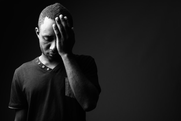 Frustrated young african man having headache in black and white