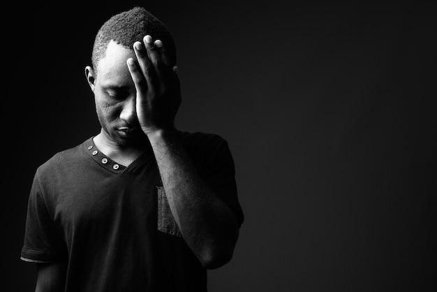 Разочарованный молодой африканец с головной болью в черно-белом