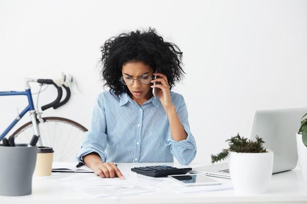 Разочарованная молодая афроамериканка-бухгалтер в стильных круглых очках