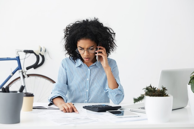 Frustrated young afro american female accountant in stylish round eyeglasses