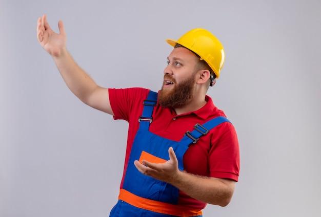 Giovane uomo barbuto frustrato del costruttore in uniforme della costruzione e casco di sicurezza che osserva in su con le braccia alzate