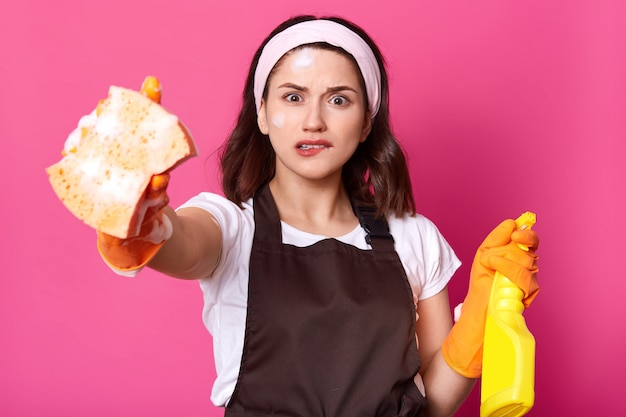 Frustrated young brunette female holds sponge and detergent, biting her lip, feeling stressed
