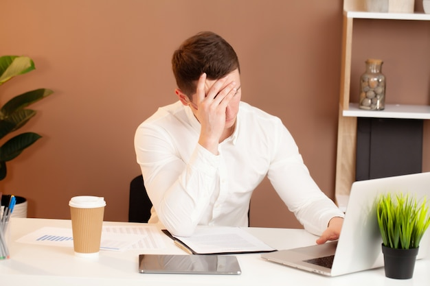 Frustrated young business man working on laptop at office