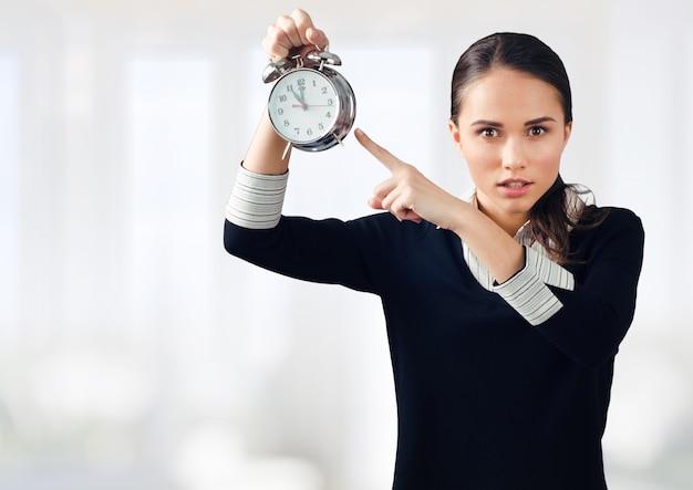 目覚まし時計を保持している欲求不満の青年実業家