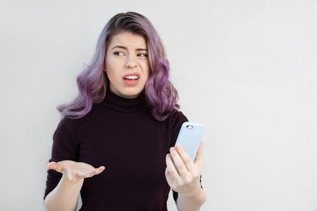 携帯電話の画面を見ている欲求不満の若いカジュアルな服装の女性。空きスペース