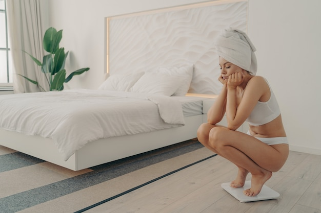 Frustrated young caucasian girl standing barefoot squatted on electronic scale in underwear after taking shower in modern bedroom next to large bed, feeling sad. weight loss and dieting concept