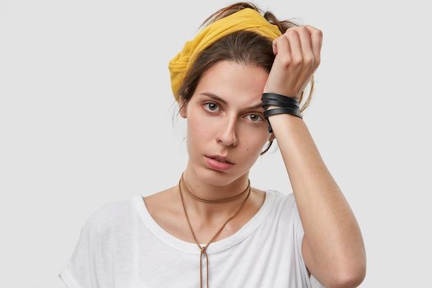 좌절 된 젊은 백인 여자가 머리에 손을 대고 노란색 스카프, 흰색 캐주얼 옷을 입고 피곤한 표정을 지으며 초과 근무를하고 집안일을합니다.