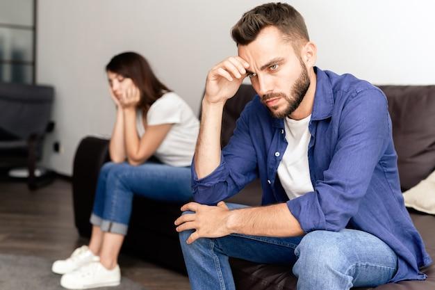 Разочарованная молодая пара обижается друг на друга, сидя на диване в гостиной и не разговаривая