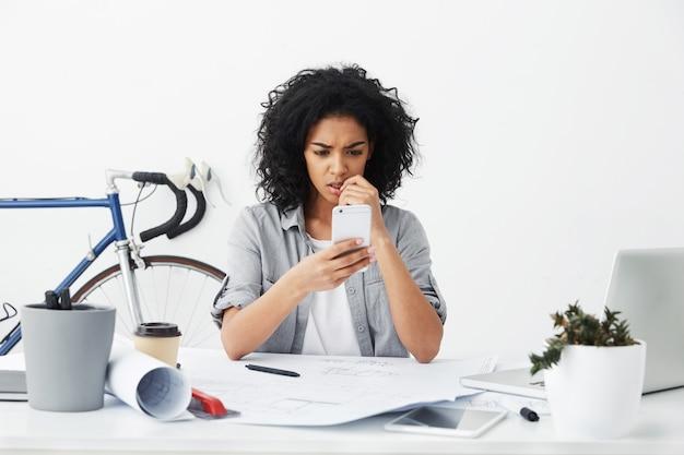 携帯電話を保持している新しいプロジェクトを設計する白いテーブルに座っている欲求不満な若い浅黒い女性