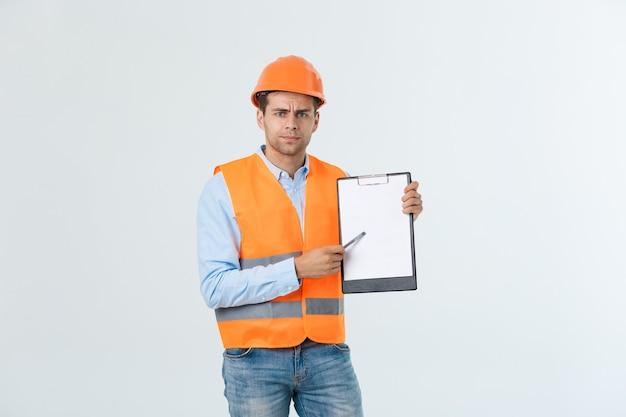 灰色の背景の上のドキュメントの間違いをチェックするヘルメットと反射ベストを持つ欲求不満の若いエンジニア。