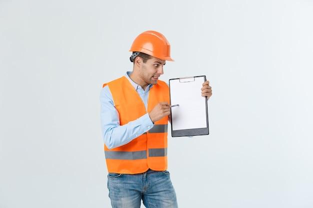 Giovane ingegnere frustrato con elmetto protettivo e giubbotto riflettente che controlla l'errore nel documento su sfondo grigio.