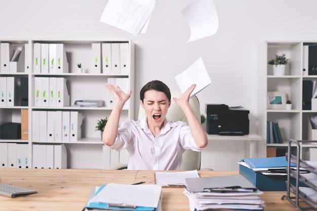 Разочарованная молодая женщина-менеджер раздражена бумагами, бросая бумаги и крича с закрытыми глазами в офисе