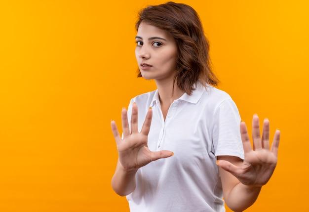 Разочарованная молодая девушка с короткими волосами в белой рубашке поло делает знак остановки с открытыми руками с серьезным лицом