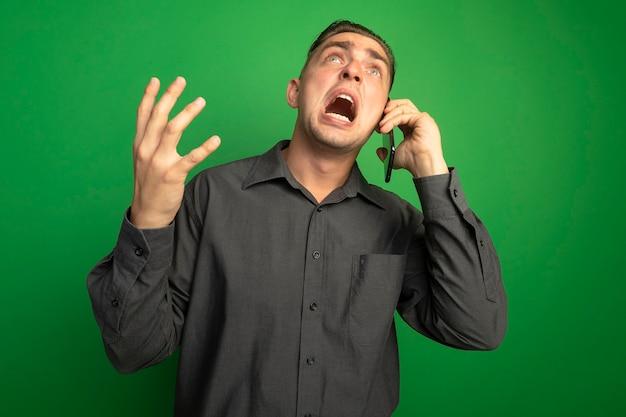 Giovane uomo bello frustrato in camicia grigia che grida e urla mentre parla sul telefono cellulare