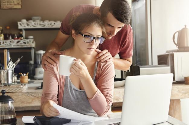 Разочарованные молодые муж и жена вместе делают документы, подсчитывают свои расходы, управляют счетами, используют портативный компьютер и калькулятор на современной кухне