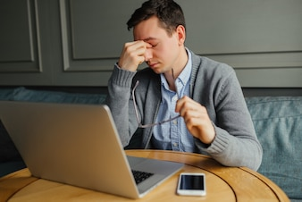Frustrated young man massaging his nose and keeping eyes closed while working