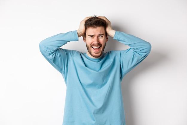 좌절 된 젊은 남자가 공황 상태에서 비명을 지르고, 흰색 배경에서 불안해하며, 당황하고 있습니다.