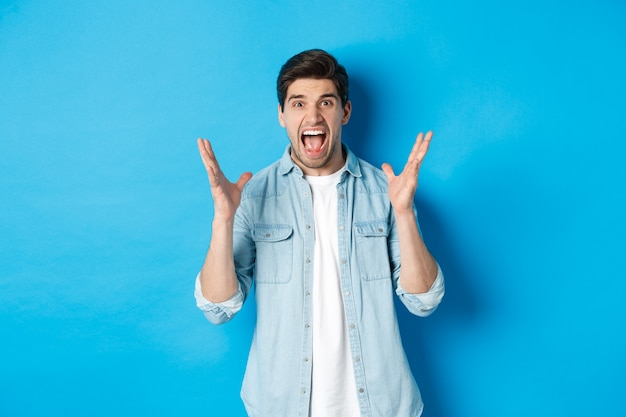 Frustrated young man screaming and looking tensed, shaking hands mad, standing against blue background
