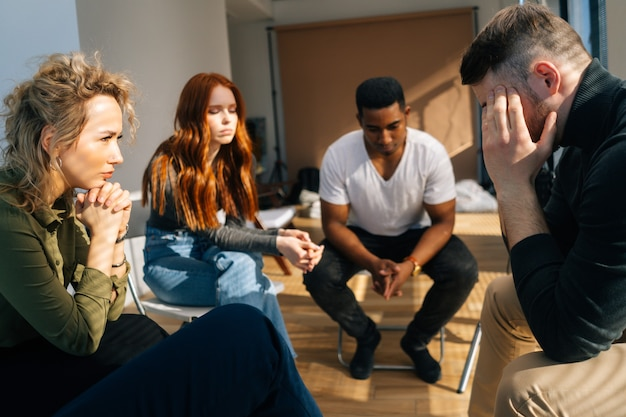 Frustrated young man sharing problem sitting in circle during group interpersonal therapy session. sad depressed male smiling telling sad story of mental problem to other patients.