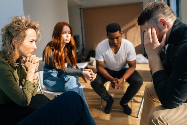 그룹 대인 관계 치료 세션 동안 원에 앉아 문제를 공유하는 좌절된 젊은 남자. 슬픈 우울한 남성은 다른 환자들에게 정신적 문제에 대한 슬픈 이야기를 하며 웃고 있습니다.