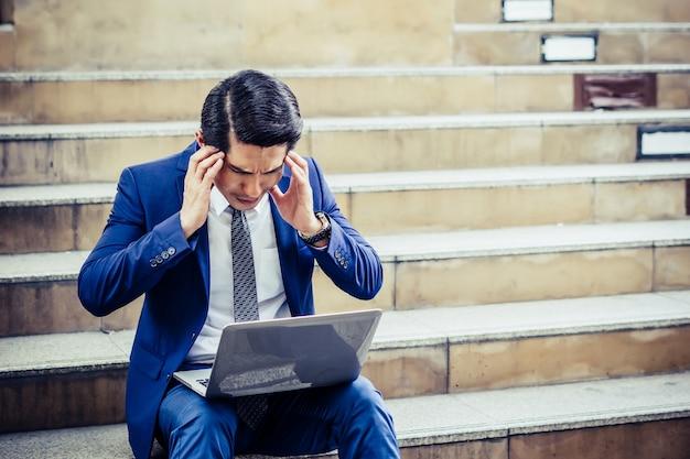 ラップトップで作業する階段に座っている挫折した若い男。不幸な仕事の問題。