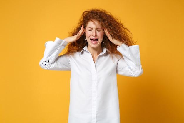 Разочарованная молодая рыжая девушка в белой рубашке позирует изолированной на желто-оранжевой стене