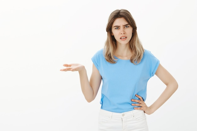 Frustrated young woman asking why, can't understand shrugging concerned