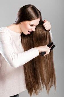 얽힌 긴 자연 머리를 빗으로 빗질하는 좌절된 젊은 여성